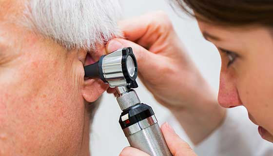 Doctor checking an old patient's ear