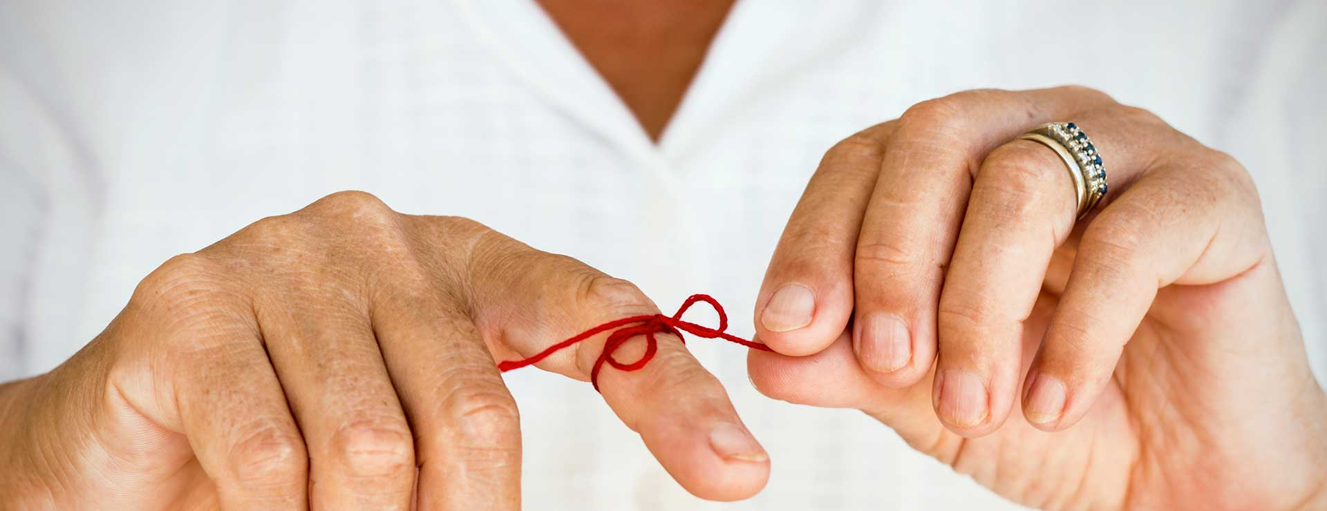 A red string tied around a finger as a reminder