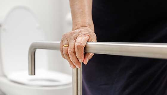Old woman holding onto a safety rail