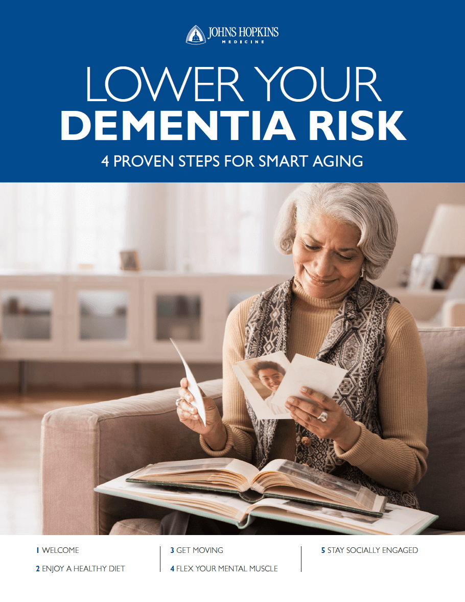 The cover of the downloadable guide to lower Dementia risks, featuring a senior woman smiling as she looks through family photographs.