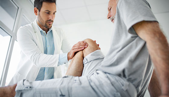 man having knee examined