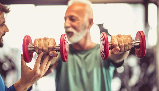 Older man in a gym lifting weights in both hands