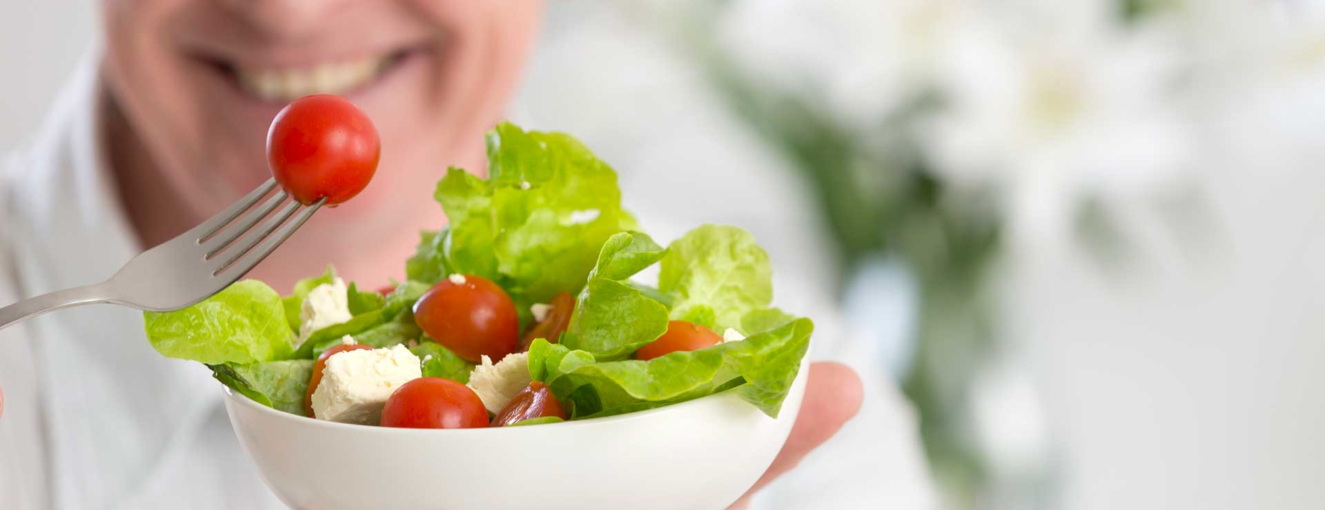 Older man holding a bowl of salad in one hand and a fork with tomato on it in the orther