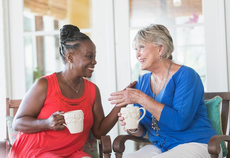 two woman socializing  and drinking coffee