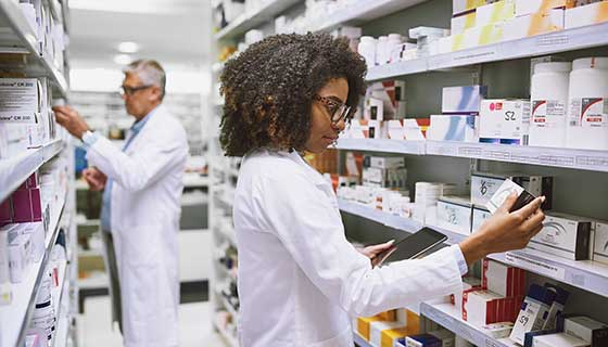 Two pharmacists looking at the medications on the shelves