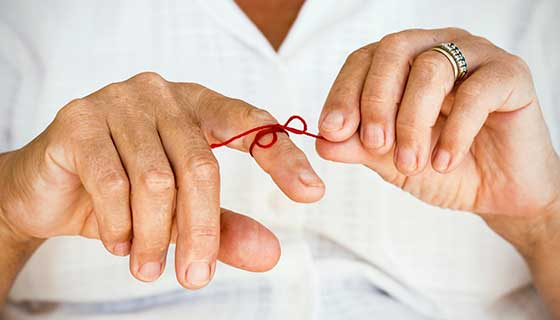 Man with a red string tied around his finger to help remember