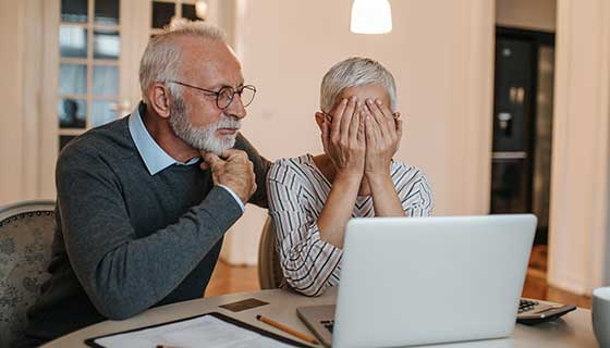 Senior couple looking at a computer stressed