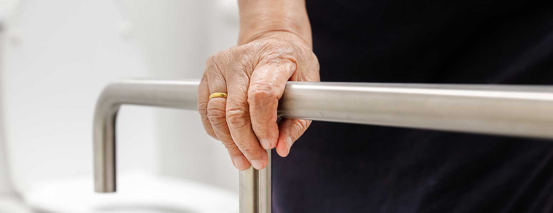 Older woman holding onto a rail