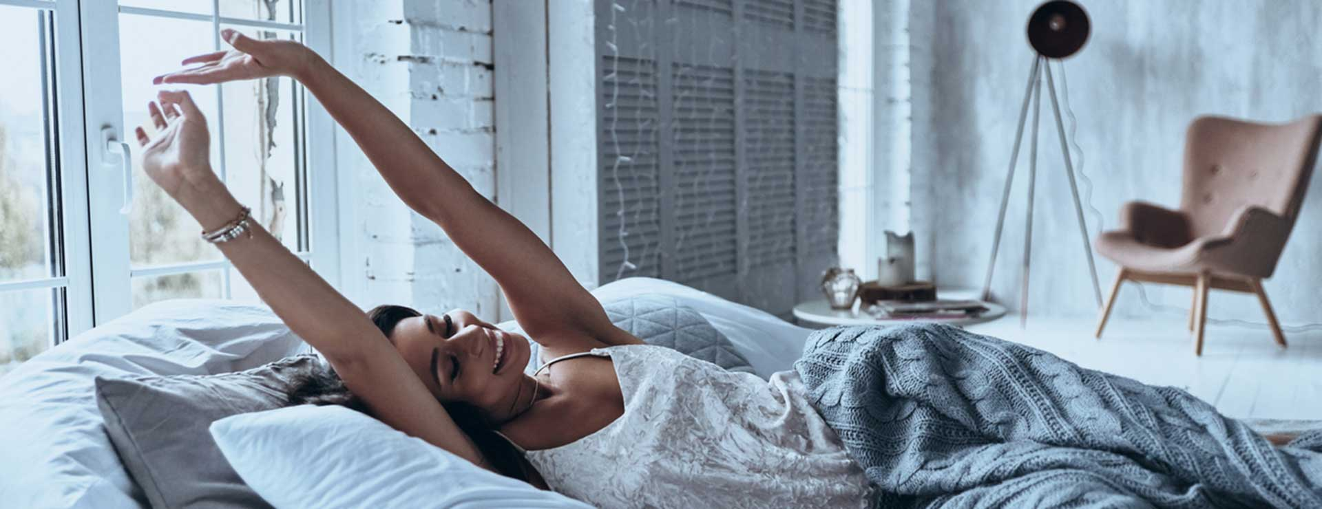 A woman stretching in bed in the morning
