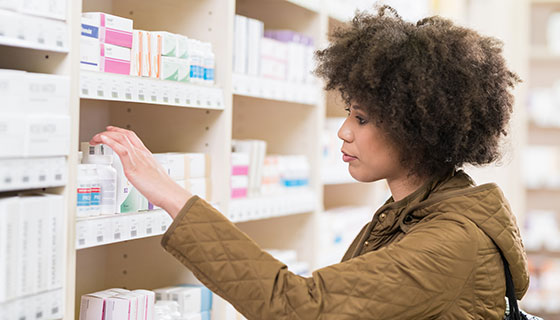 Woman browsing a pharmacy aisle.