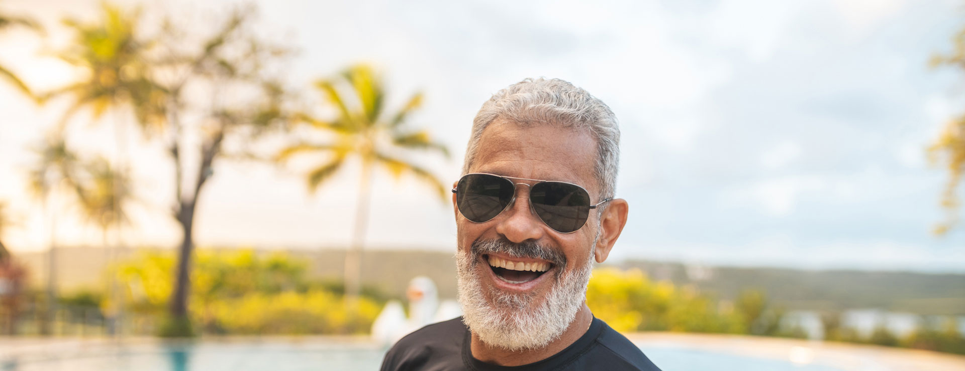 A senior man smiles outdoors while wearing sunglasses