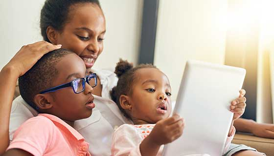 Boy wearing glasses and looking at an iPad with his mother and sister