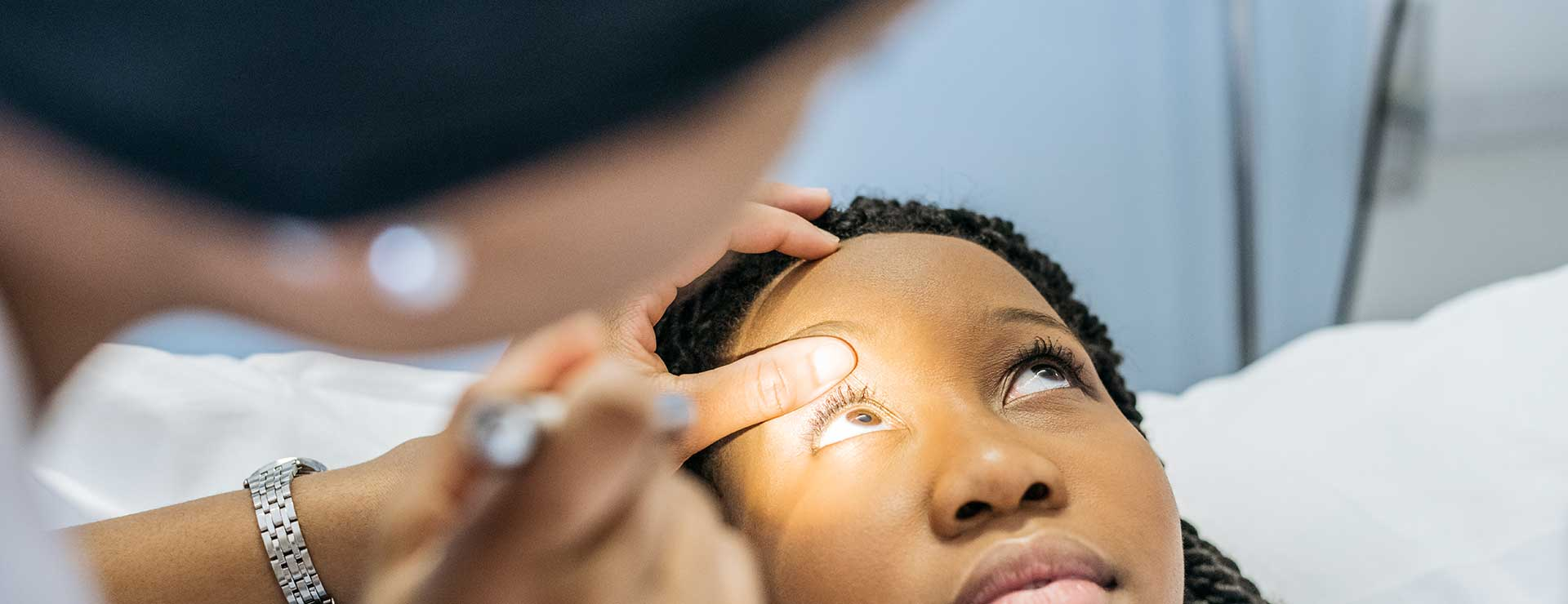 a doctor shines a light into eye of female patient