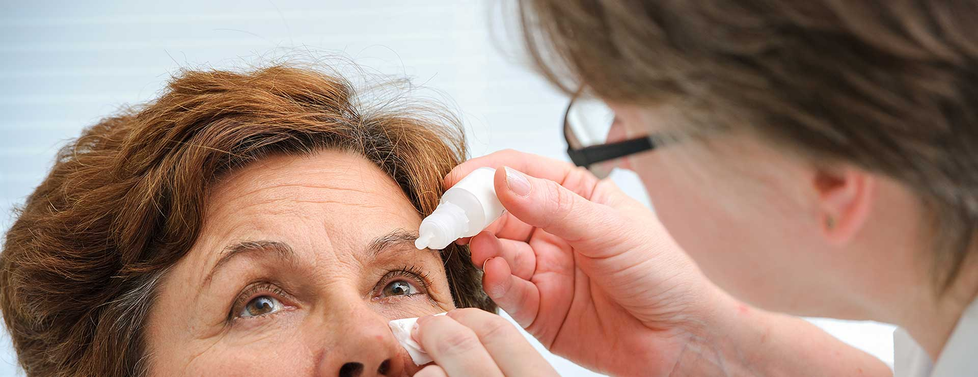 A senior woman receives eye drops from doctor