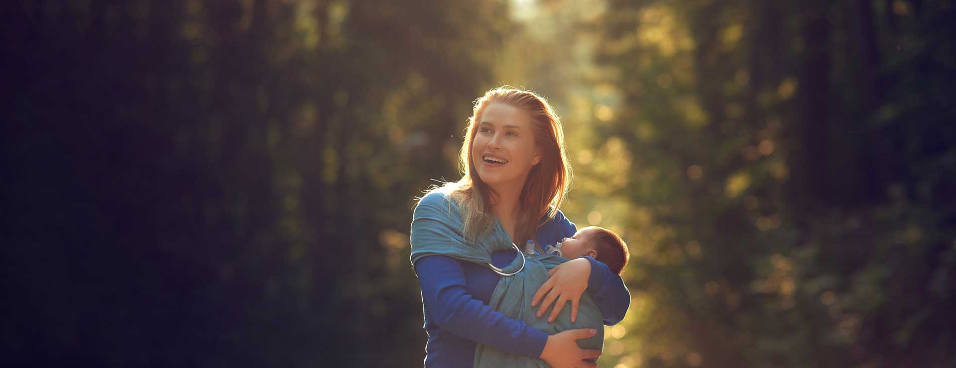Happy woman carrying a baby outdoors