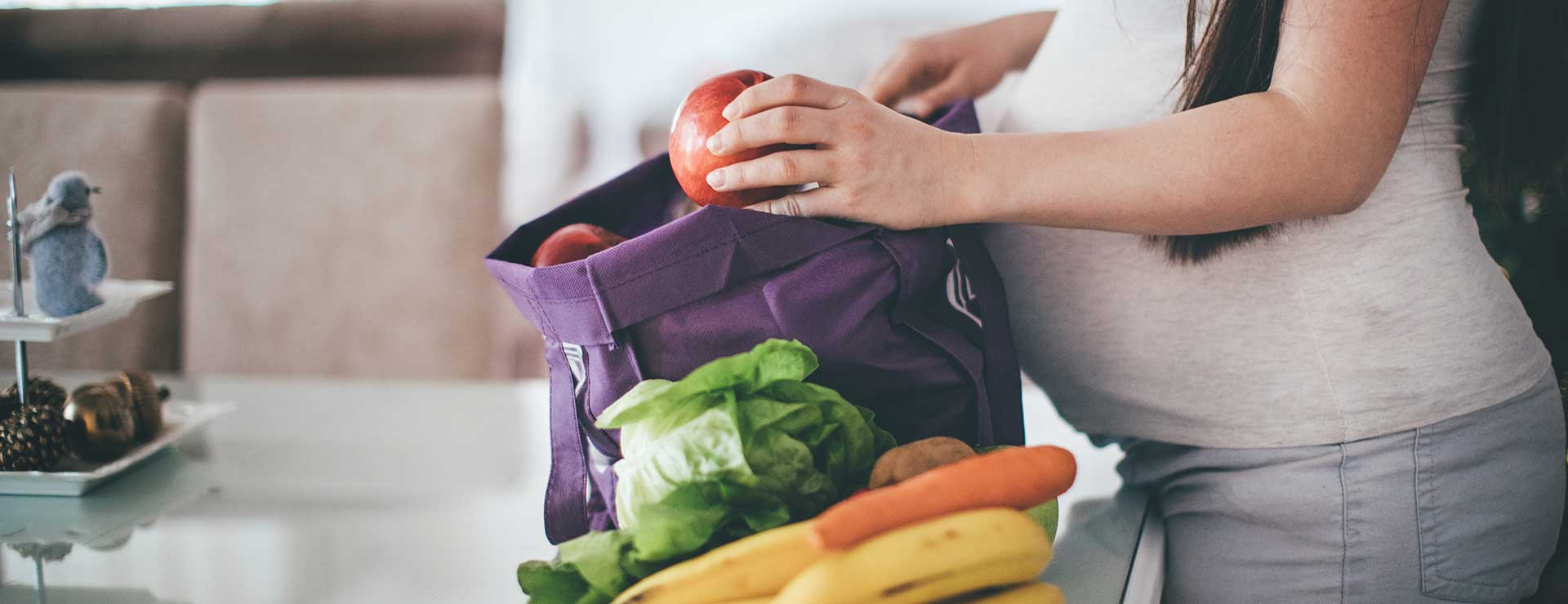 pregnant woman packing unpacking groceries