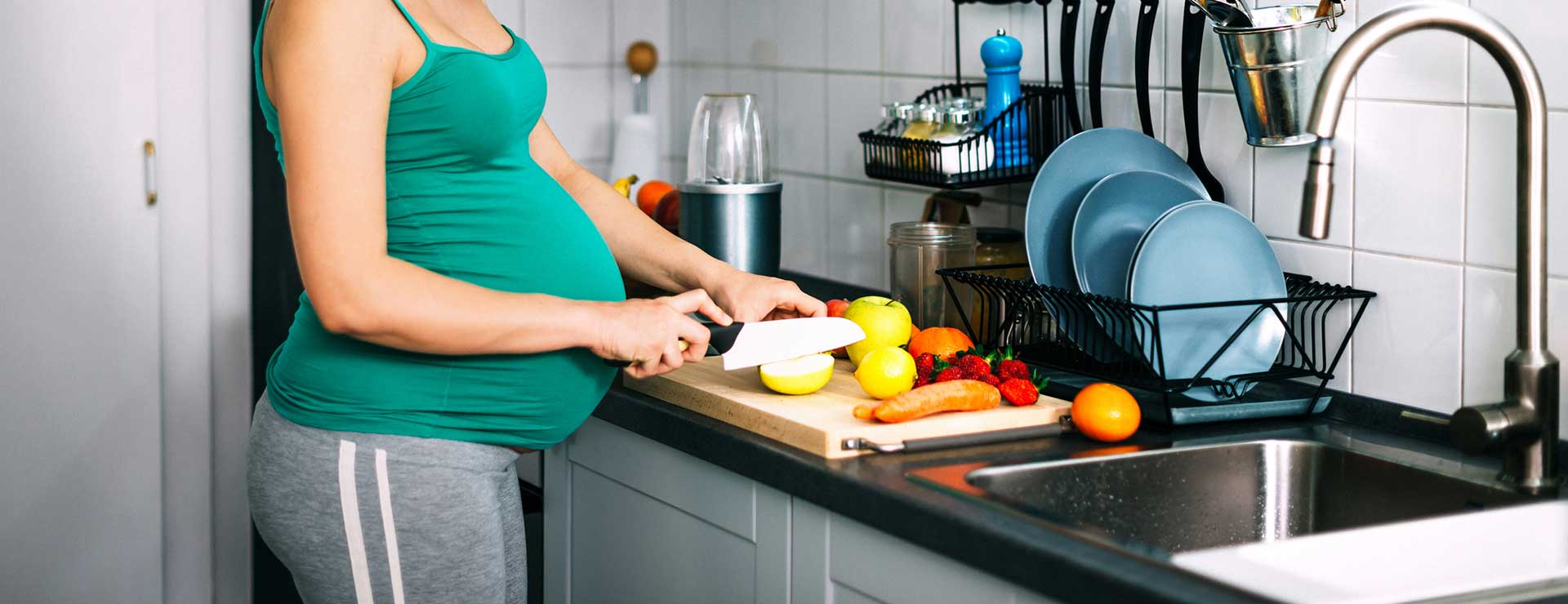 A pregnant woman cuts fruit for a smoothie.