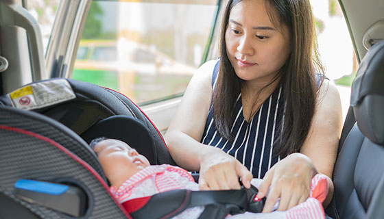 woman buckling baby in carseat