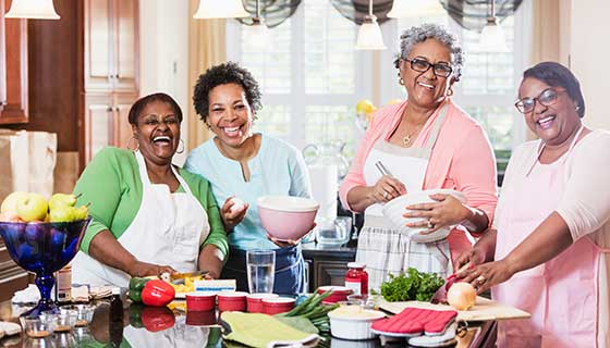 A group of women laugh together as they cook holiday dinner.