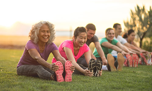 A group of smiling adults stretch before exercising.
