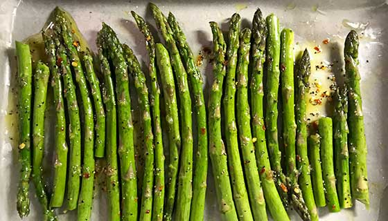 Rosemary asparagus on a baking sheet