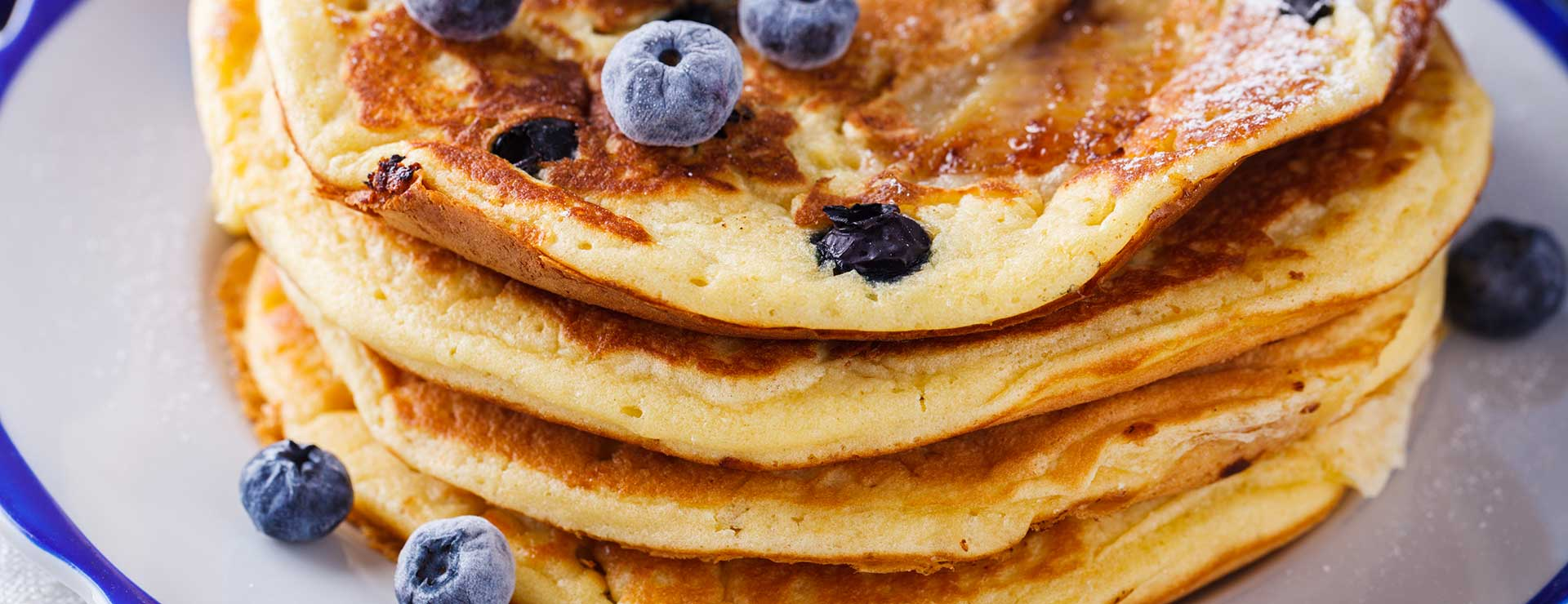 A plate of pancakes with blueberries on top.