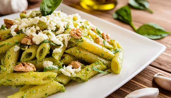 A plate of pesto pasta topped with cheese and walnuts.