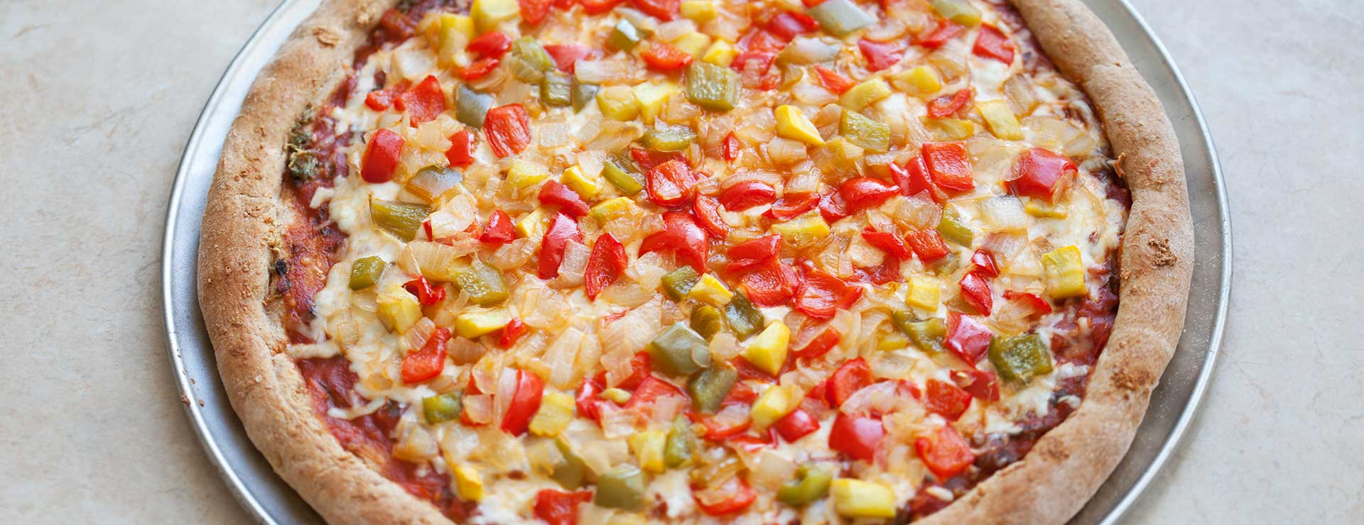 pizza on wheat crust with peppers and onions