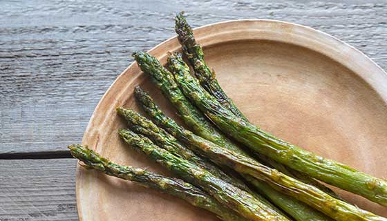Roasted asparagus on a wooden plate.