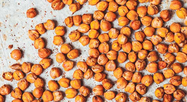Roasted chickpeas splayed across a baking sheet.