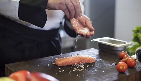 a chef seasons a fresh salmon filet