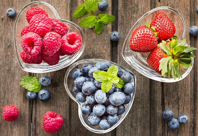 Berries in heart-shaped glass bowls.