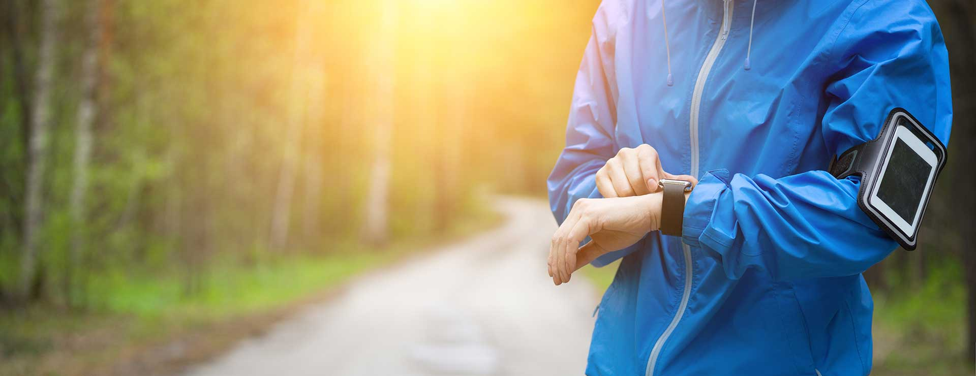 Woman on a running trail checks fitness tracker