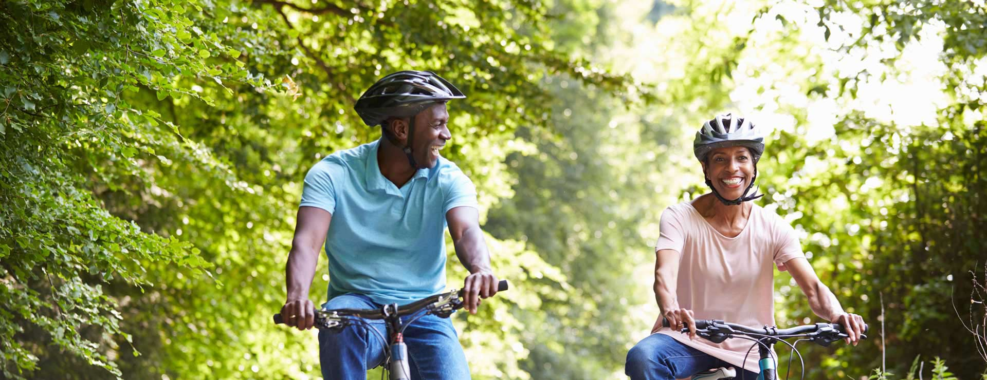Couple riding bikes together on a wooded path.