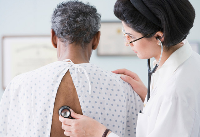 A doctor using a stethoscope on a patient's back.