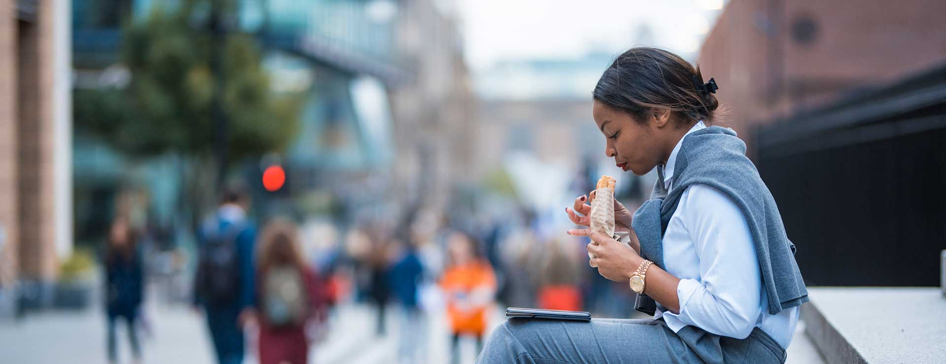A woman sitting on the steps of a building and eating a wrap while looking at her tablet
