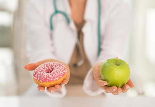 A doctor holds a donut in one hand and an apple in the other.