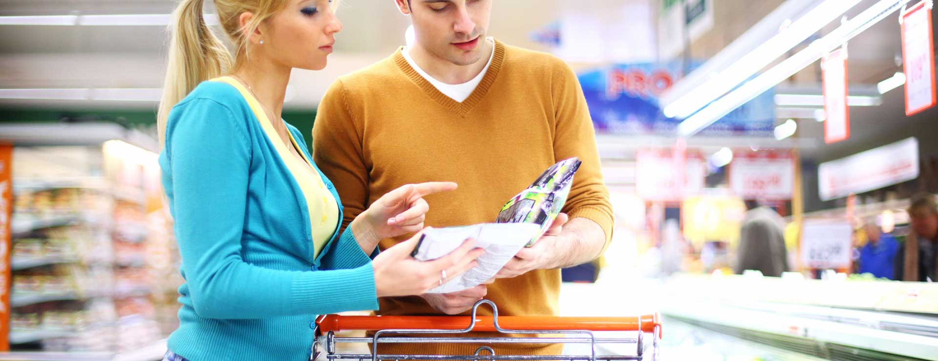 A young couple comparing food labels in a grocery store