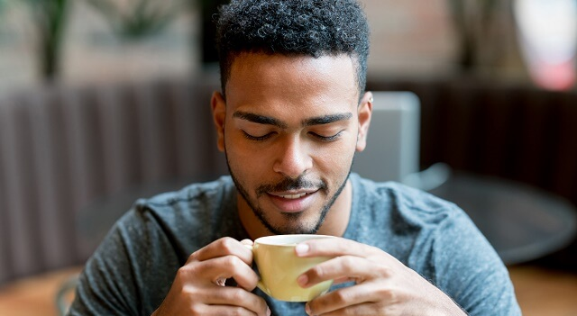 A young man drinks a cup of coffee in a cafe.