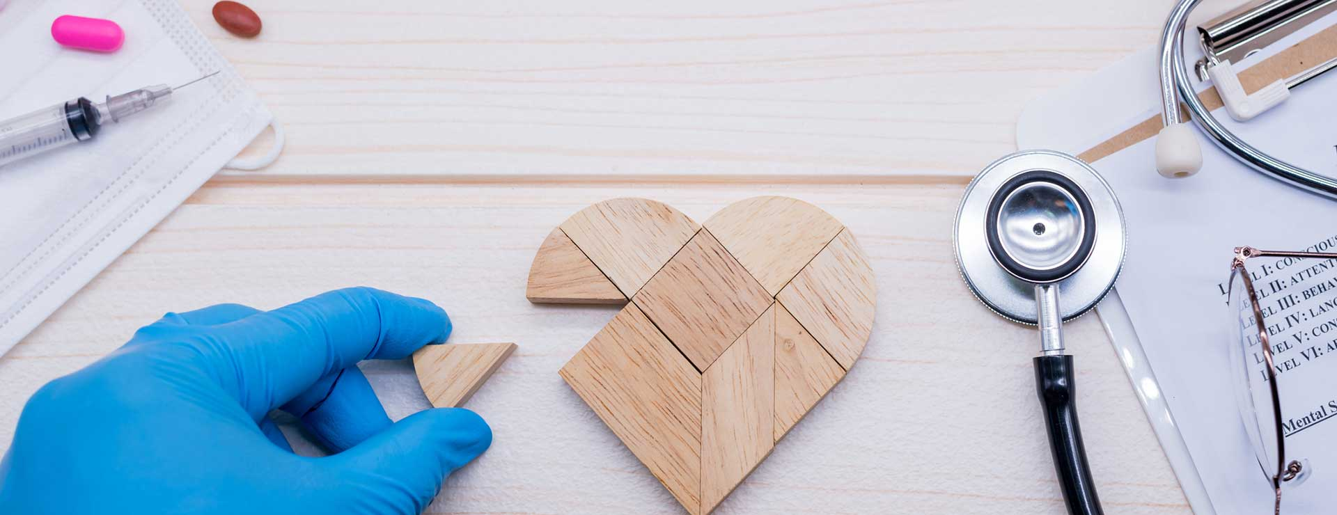 A doctor putting together a wooden heart-shaped puzzle
