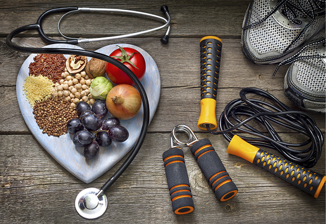 An arrangement of healthy foods on a heart-shaped plate surrounded by exercise equipment