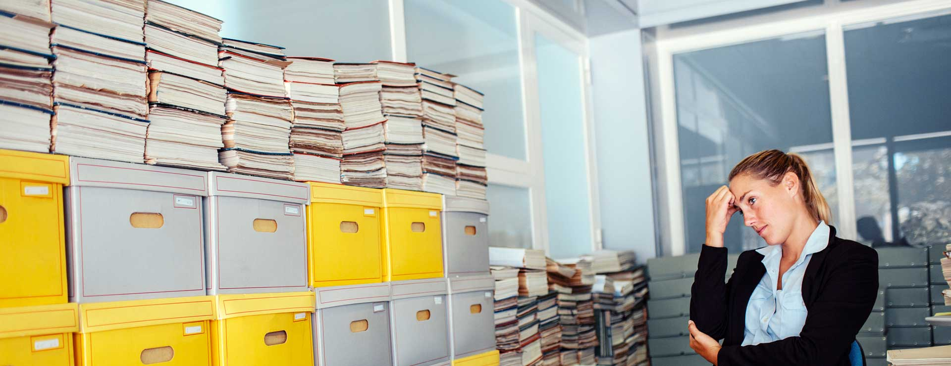Woman stressed at work looking at a shelf full of files