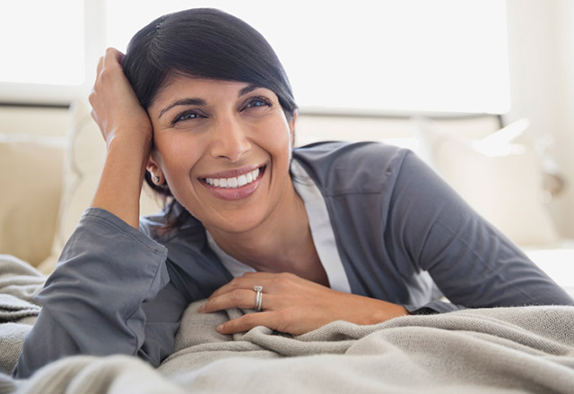 Woman relaxes in bed