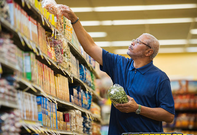 A man reaches for the top shelf in a grocery store