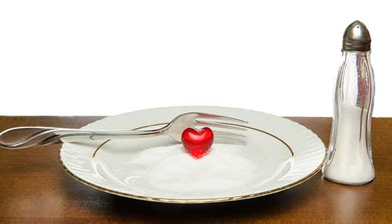 A plate of salt with a red heart figurine on it