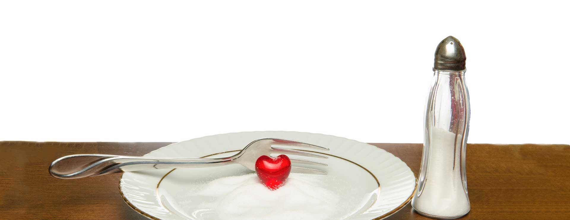 A plastic heart on a plate full of salt