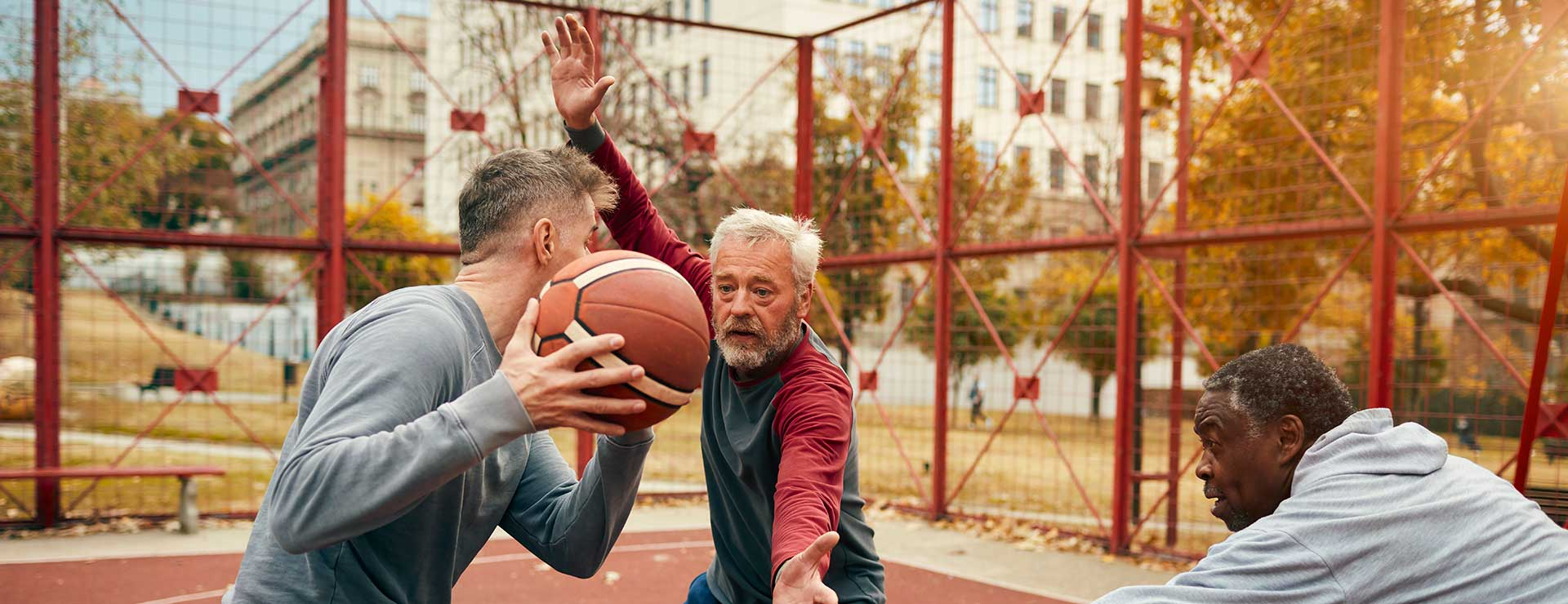 A group of seniors play basketball outdoors
