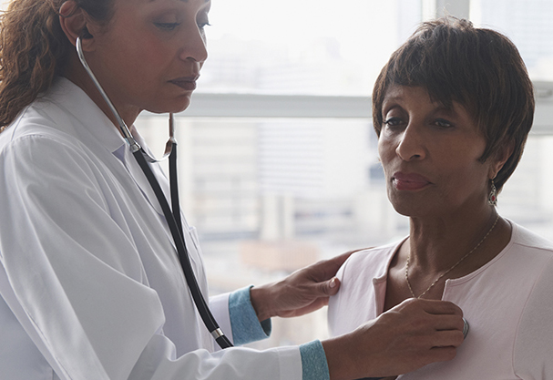Doctor listening for a woman's heartbeat