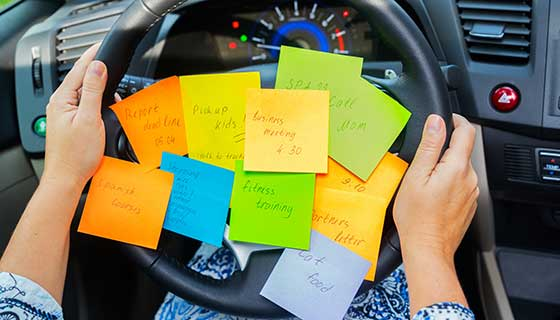 Sticky notes with to-do items on a steering wheel