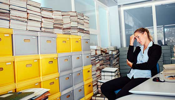 Stressed woman at work looking at full file cabinets